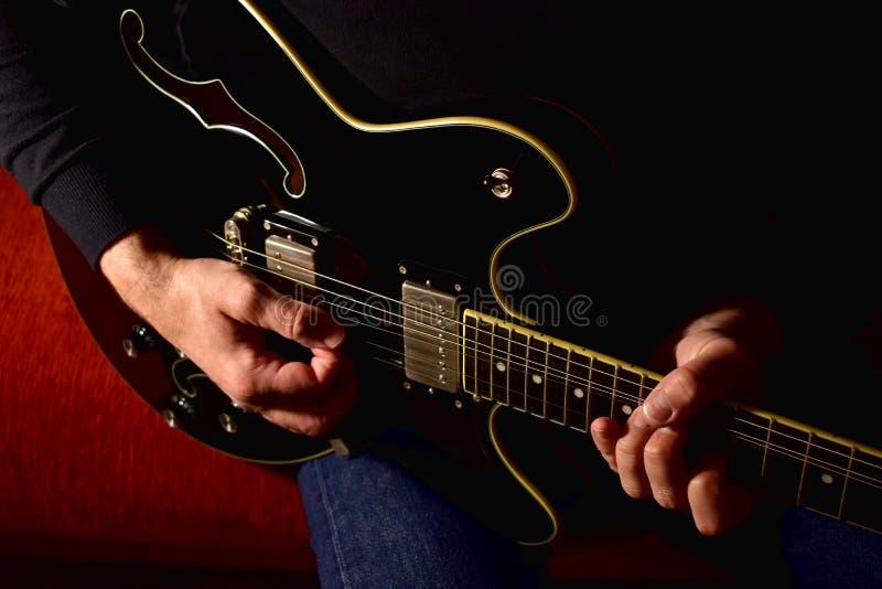 Hombre que toca una guitarra eléctrica Primer, ninguna cara fotografía de archivo