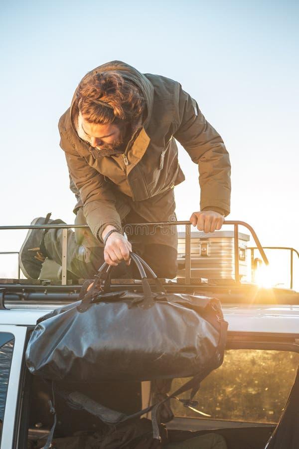 Hombre que toma el equipaje del tejado de una furgoneta fotos de archivo