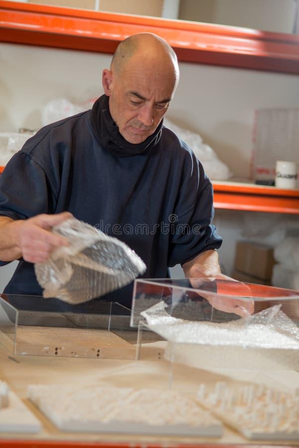Hombre que toma el plástico de burbujas de un caso de acrílico foto de archivo libre de regalías