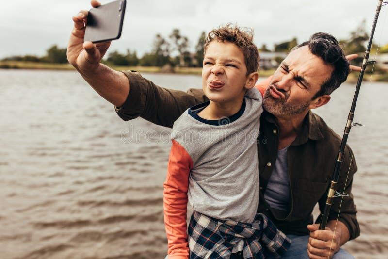 Hombre que toma el selfie con su niño al aire libre fotografía de archivo