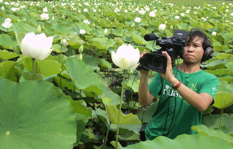 Hombre que toma el video en granja del loto imagen de archivo libre de regalías