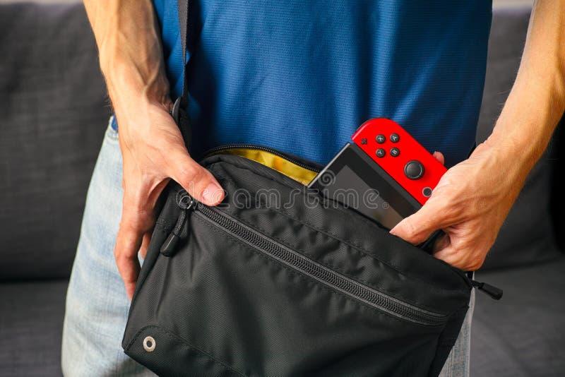 Hombre que toma la consola del videojuego del interruptor de Nintendo del bolso negro imagenes de archivo