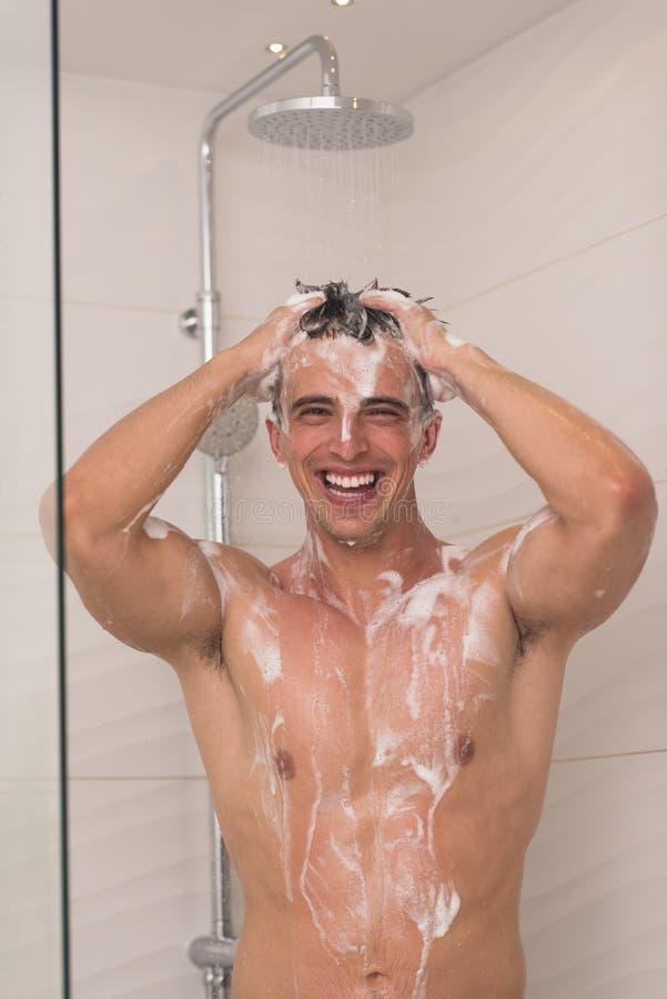 Hombre que toma la ducha en baño imagen de archivo