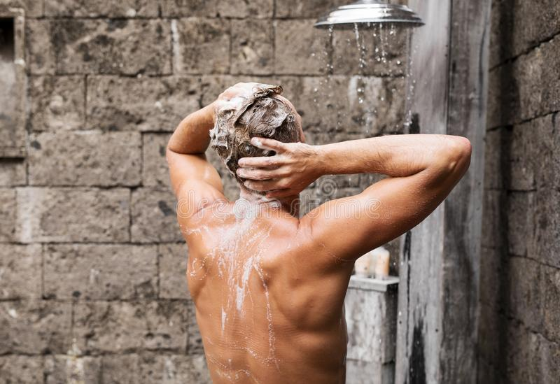 Hombre que toma la ducha y que lava el pelo fotos de archivo libres de regalías