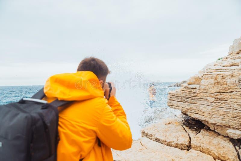 Hombre que toma la imagen de la mujer en impermeable amarillo en el acantilado cerca del mar foto de archivo libre de regalías