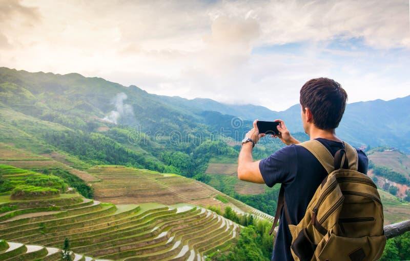 Hombre que toma la imagen del paisaje asiático imponente de la terraza del arroz imagen de archivo libre de regalías