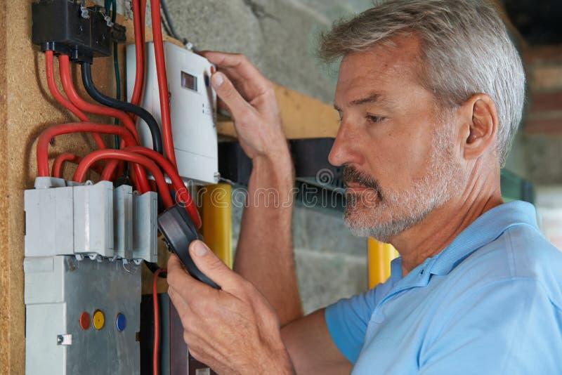 Hombre que toma la lectura del metro de la electricidad imagenes de archivo