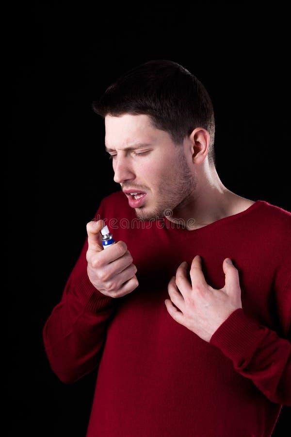 Hombre que toma la medicina para la garganta dolorida imagen de archivo