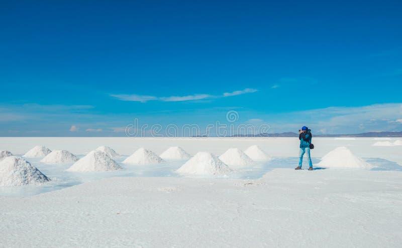 Hombre que toma las fotos de los bancos de la sal en Salar de Uyuni foto de archivo