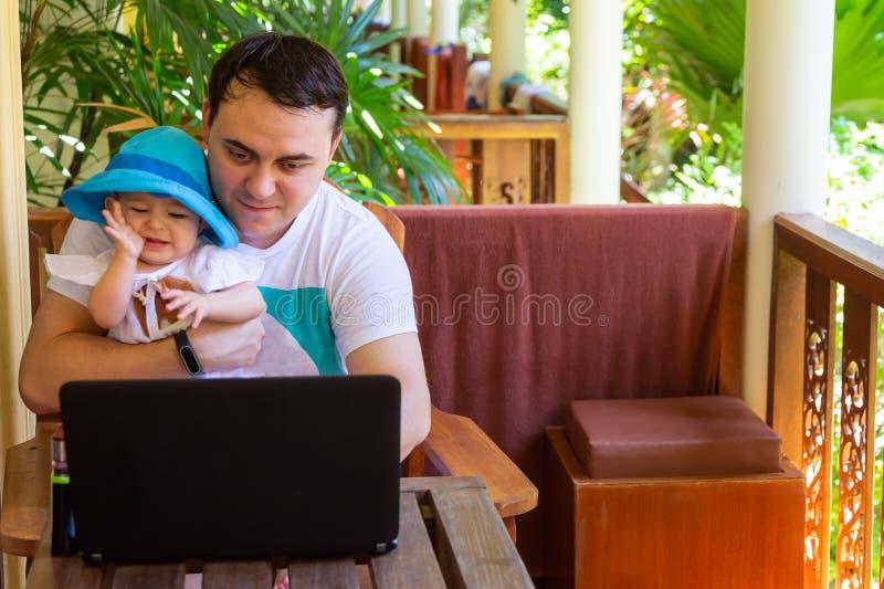 Hombre que trabaja con el cuaderno en viaje Padre con el niño en las manos Cuidado del trabajo y del bebé fotos de archivo