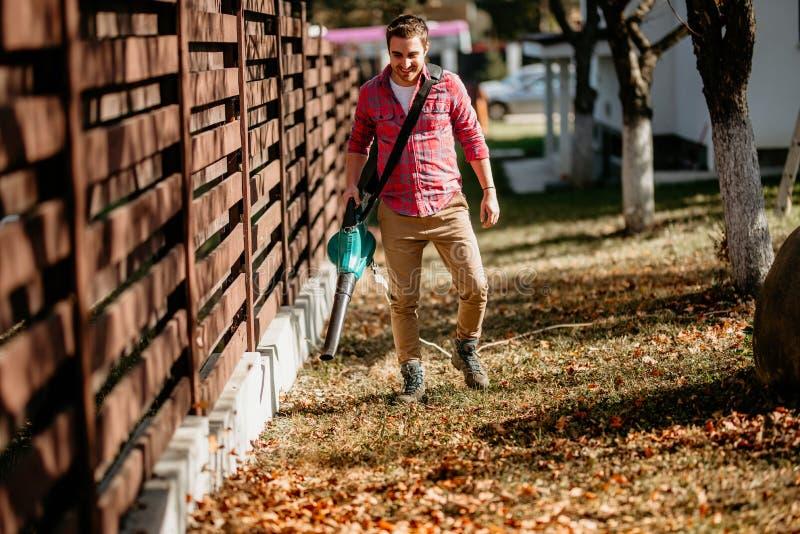 Hombre que trabaja con el ventilador de hoja en patio trasero foto de archivo