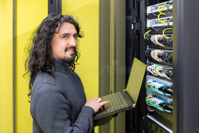Hombre que trabaja con los servidores en centro de datos foto de archivo libre de regalías