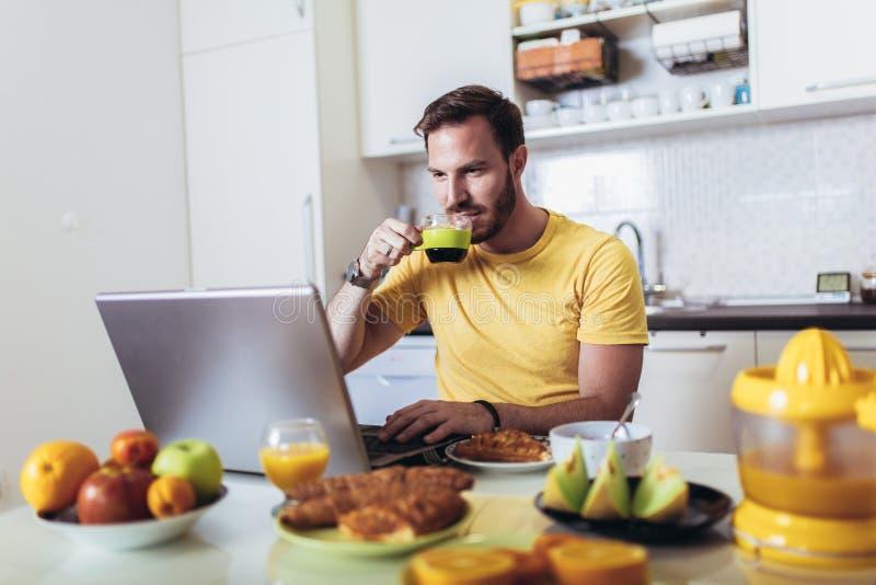 Hombre que trabaja en casa, usando el ordenador portátil mientras que desayunando fotografía de archivo