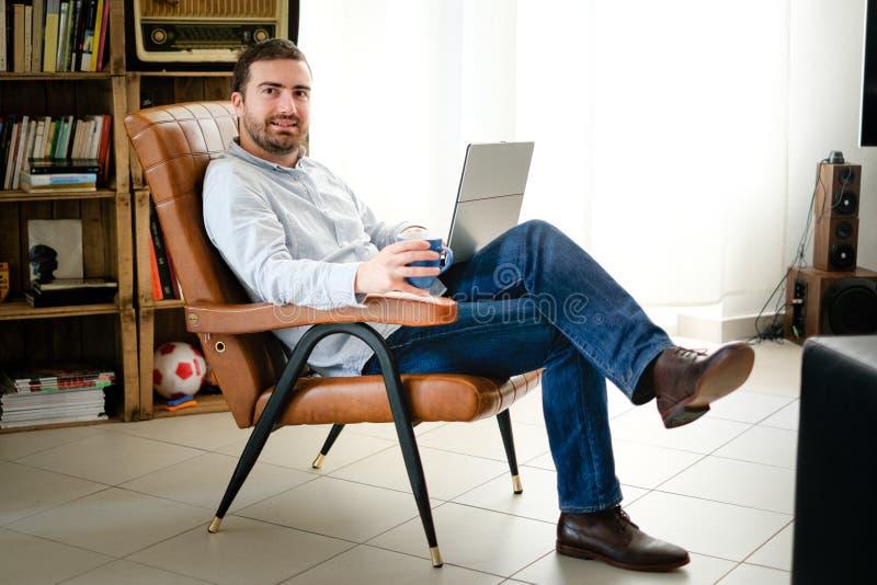 Hombre que trabaja en casa usando su ordenador portátil fotos de archivo libres de regalías