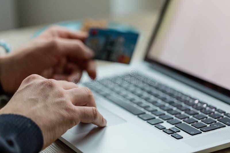 Hombre que trabaja en el cuaderno con la tarjeta de crédito imagenes de archivo