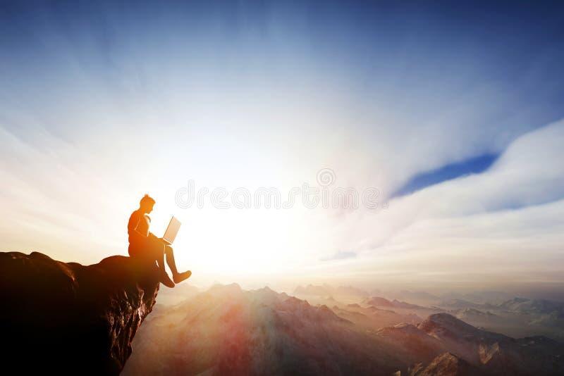 Hombre que trabaja en el cuaderno encima de las montañas Libertad de Internet imágenes de archivo libres de regalías