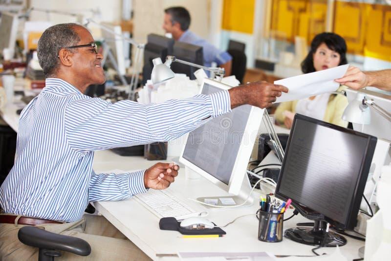 Hombre que trabaja en el escritorio en oficina creativa ocupada imagenes de archivo