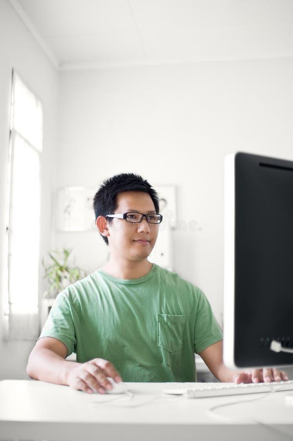Hombre que trabaja en el ordenador imagen de archivo libre de regalías