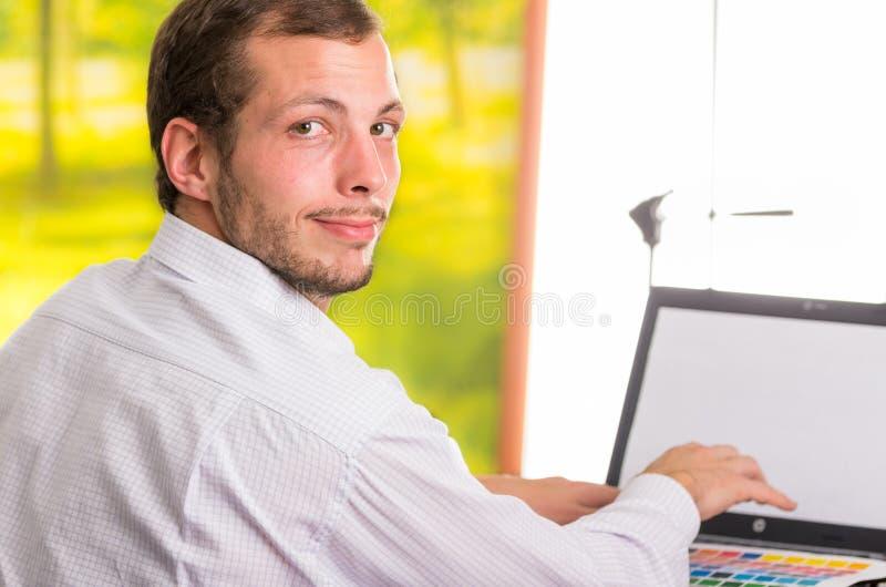 Hombre que trabaja en el ordenador portátil que da vuelta alrededor hacia foto de archivo libre de regalías