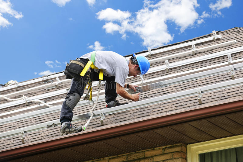Hombre que trabaja en la azotea que instala los paneles solares imagen de archivo