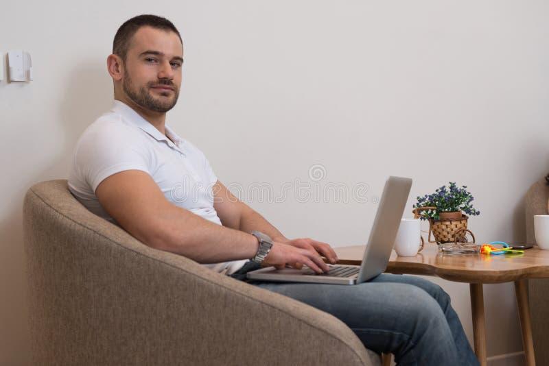 Hombre que trabaja en la computadora portátil en el país imagen de archivo