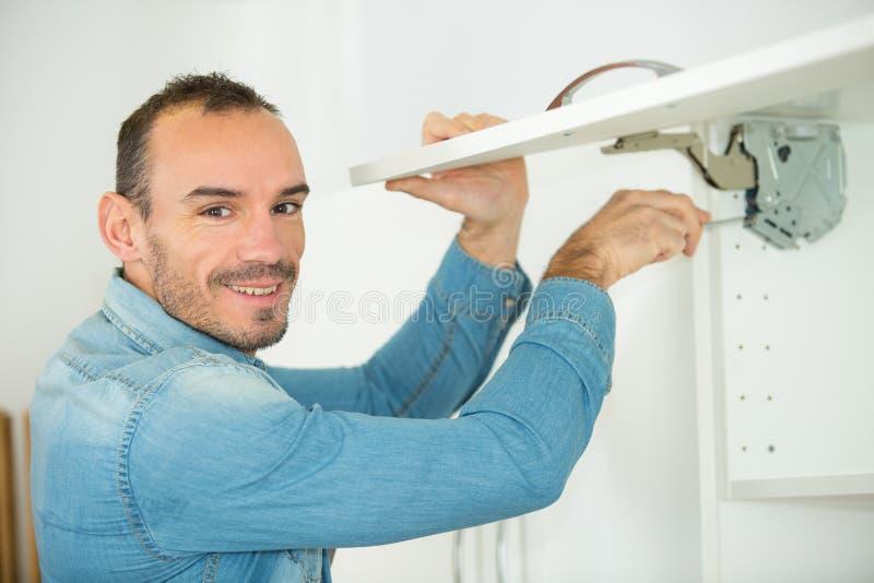 Hombre que trabaja en la nueva instalaci?n de la cocina imagenes de archivo