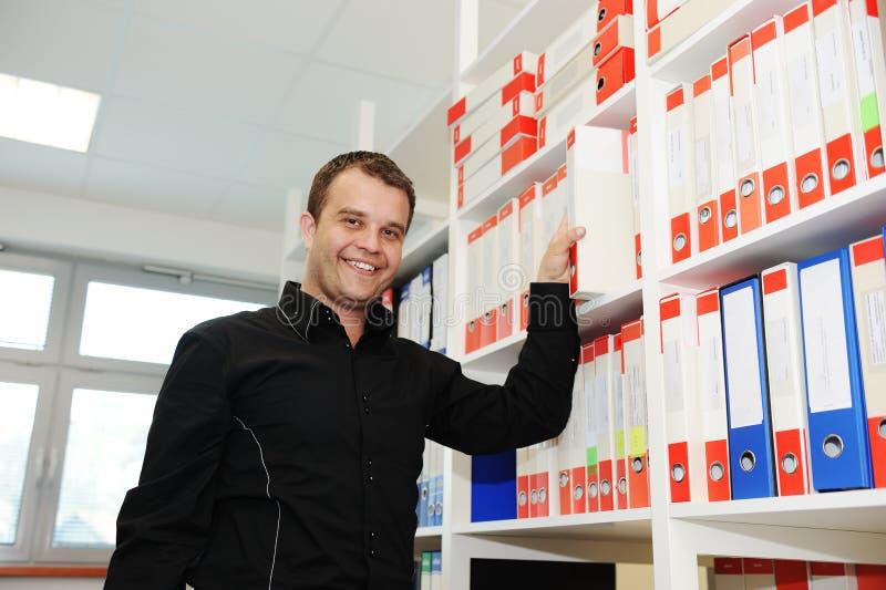 Hombre que trabaja en la oficina que pone carpetas juntas imagen de archivo libre de regalías