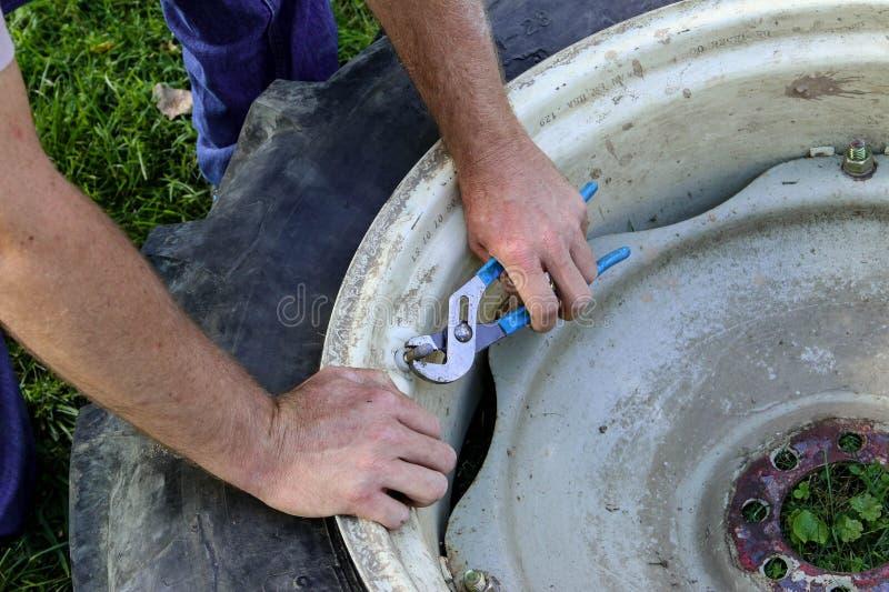 Hombre que trabaja en la reparación del neumático del tractor fotos de archivo libres de regalías