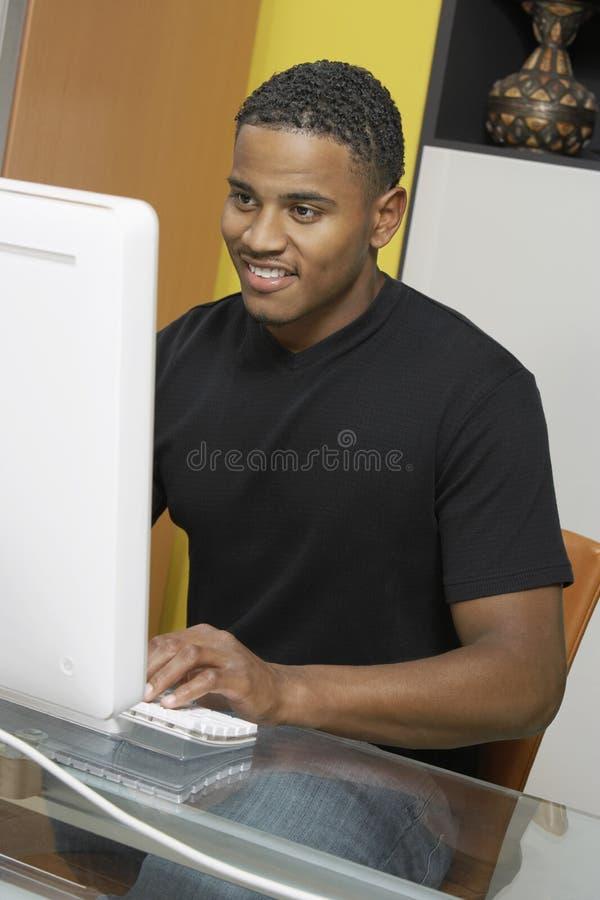 Hombre que trabaja en PC de sobremesa fotografía de archivo