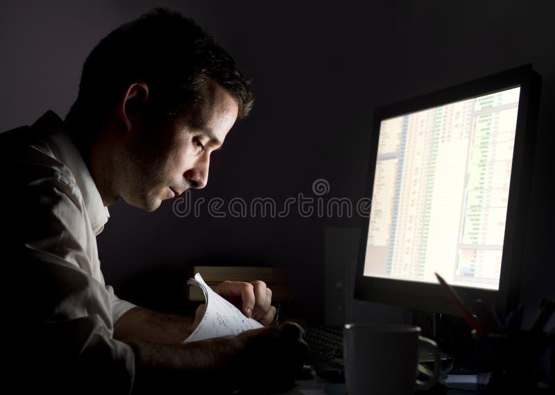 Hombre que trabaja tarde foto de archivo