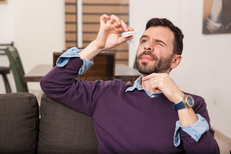 Hombre que usa algunos descensos de ojo en casa fotos de archivo