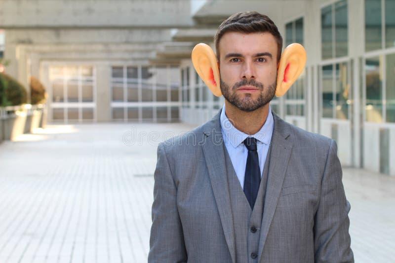Hombre que usa el audífono en la oficina fotografía de archivo