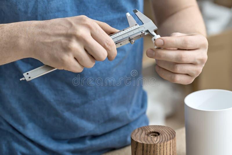 Hombre que usa el calibrador en taller foto de archivo libre de regalías