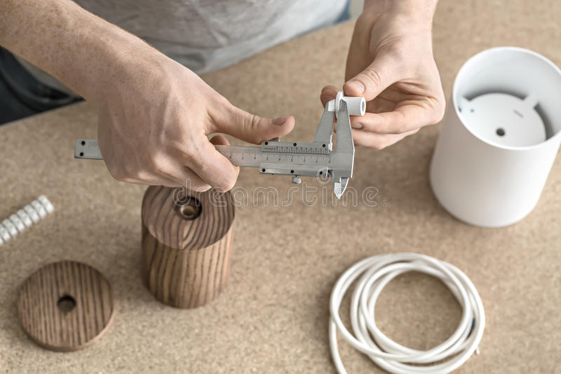 Hombre que usa el calibrador en taller imagen de archivo libre de regalías