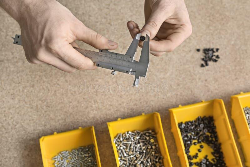 Hombre que usa el calibrador en taller imagenes de archivo
