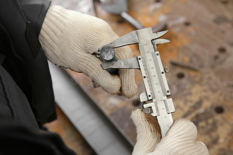 Hombre que usa el calibrador a vernier para la barra de metal de medición fotos de archivo
