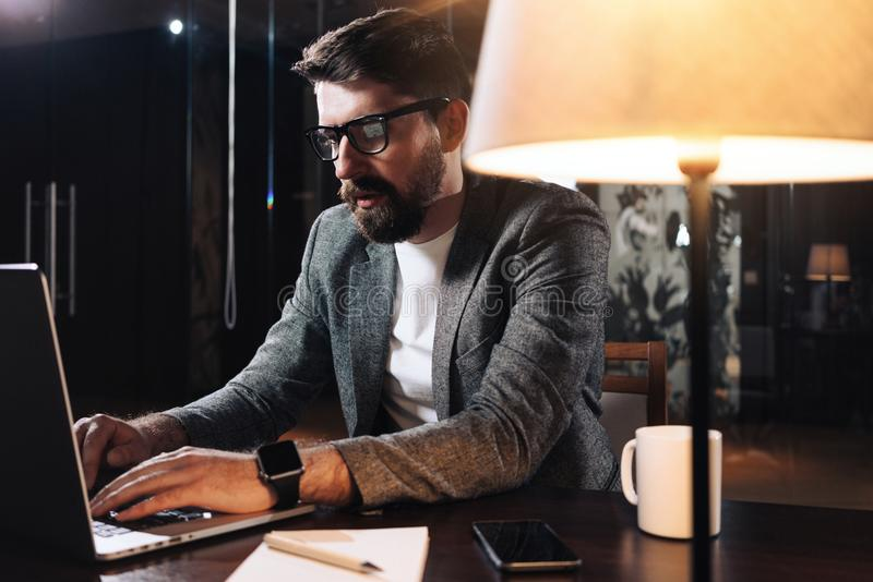 Hombre que usa el cuaderno móvil contemporáneo Hombre de negocios barbudo que trabaja en la noche en oficina moderna del desván E imagen de archivo libre de regalías