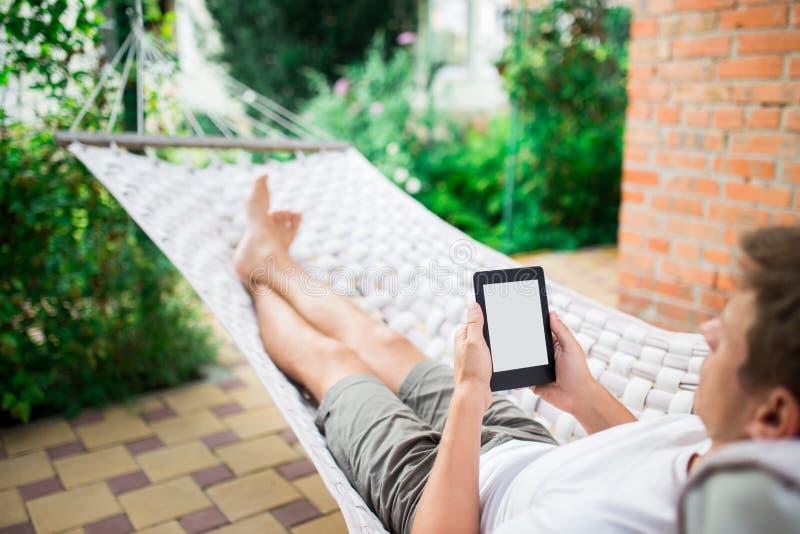 Hombre que usa el eBook o la tableta mientras que se relaja en una hamaca imagenes de archivo
