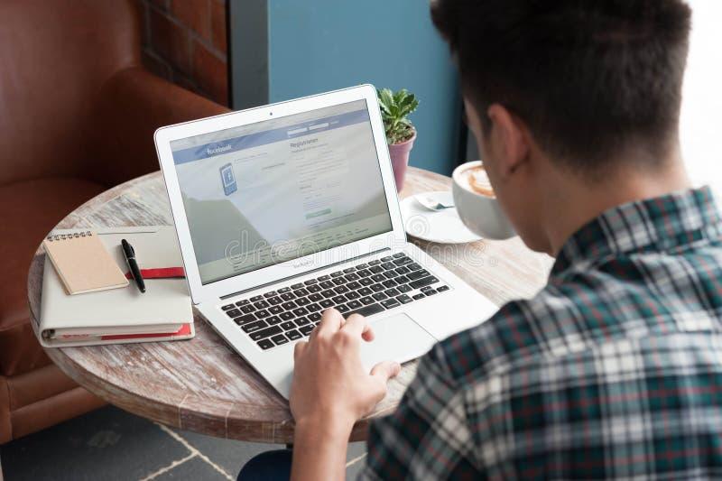 Hombre que usa el ordenador portátil, inicio de sesión en la cuenta de Facebook imagen de archivo