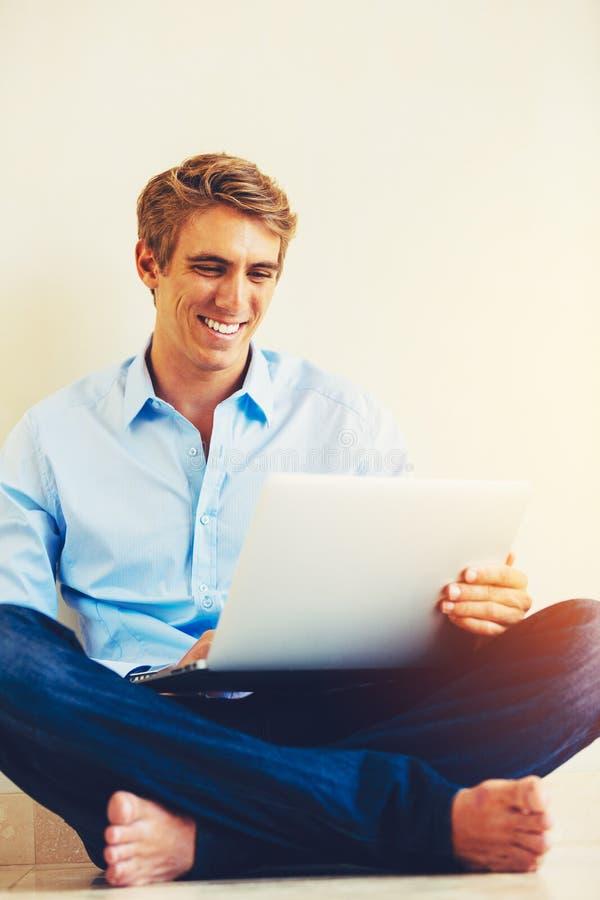 Hombre que usa el ordenador portátil que trabaja de hogar fotografía de archivo libre de regalías