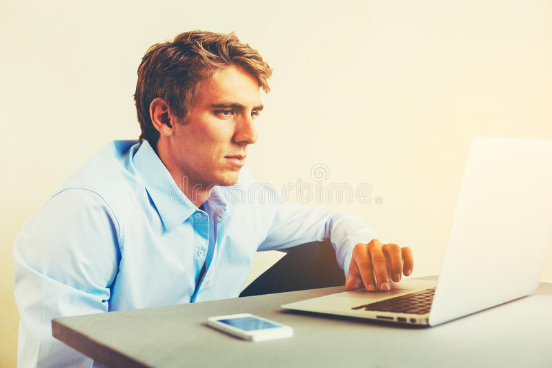 Hombre que usa el ordenador portátil que trabaja de hogar imagen de archivo libre de regalías