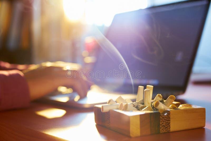 Hombre que usa el ordenador portátil y fumando el cigarrillo en la mañana fotos de archivo