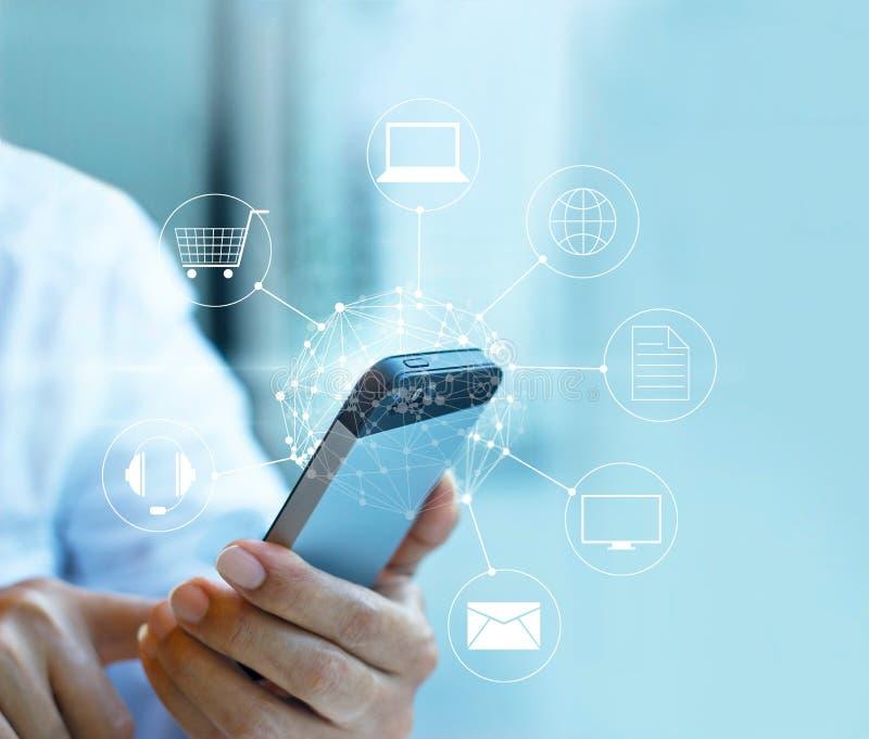 Hombre que usa el pago móvil, llevando a cabo el círculo conexión global y del icono del cliente de red, canal de Omni foto de archivo libre de regalías