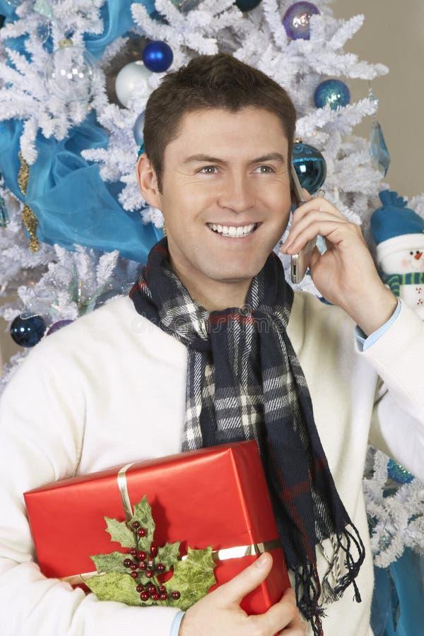 Hombre que usa el teléfono celular que se sostiene presente por el árbol de navidad imagen de archivo