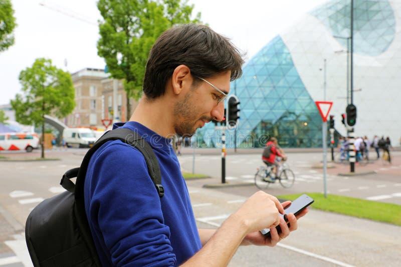 Hombre que usa el teléfono móvil app en calle urbana moderna de la ciudad Hombre caucásico joven que sostiene el smartphone para  imagenes de archivo