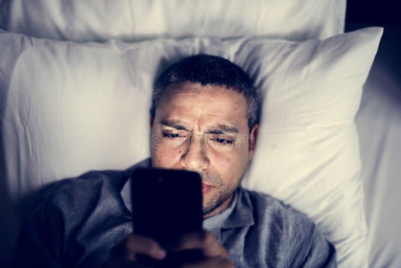 Hombre que usa el teléfono móvil en cama imágenes de archivo libres de regalías