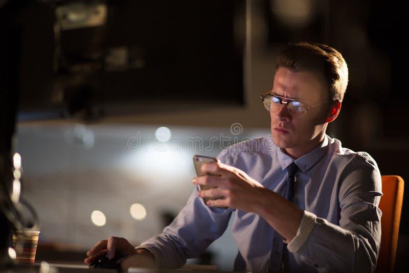Hombre que usa el teléfono móvil en oficina oscura fotografía de archivo