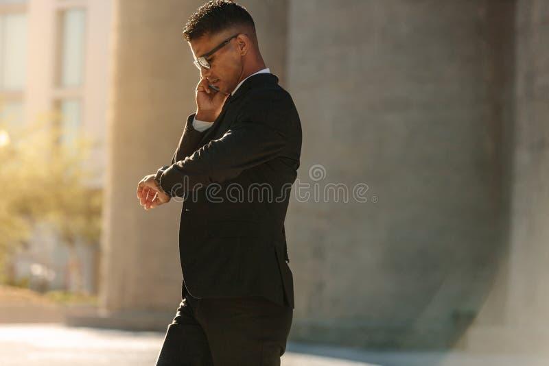 Hombre que usa el teléfono móvil mientras que camina en la calle imagen de archivo