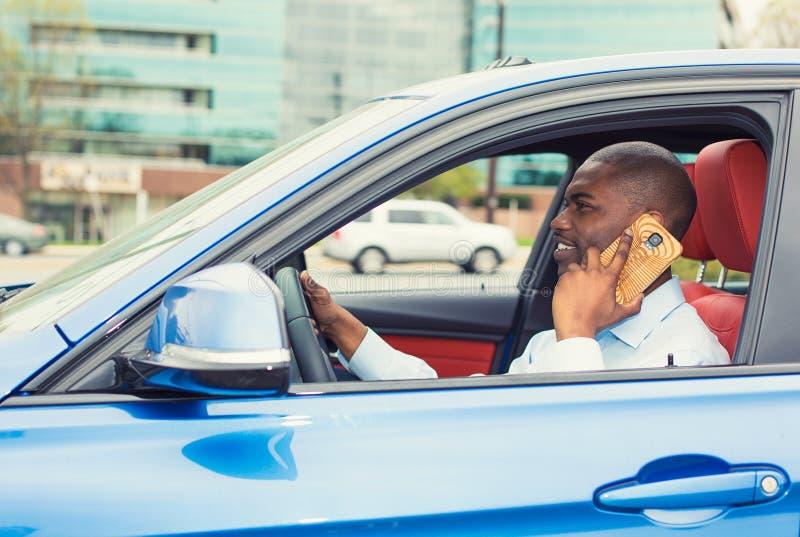 Hombre que usa el teléfono móvil mientras que conduce el coche al trabajo foto de archivo libre de regalías