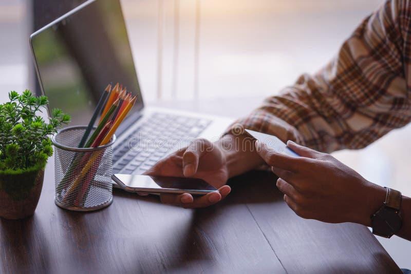 Hombre que usa el teléfono móvil y el ordenador portátil para hacer compras en línea por crédito imágenes de archivo libres de regalías